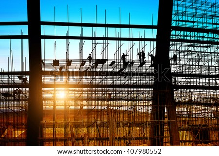 Construction workers working on scaffolding, dusk picture. - stock photo