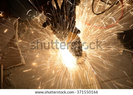 construction working grinding a piece of metal - stock photo