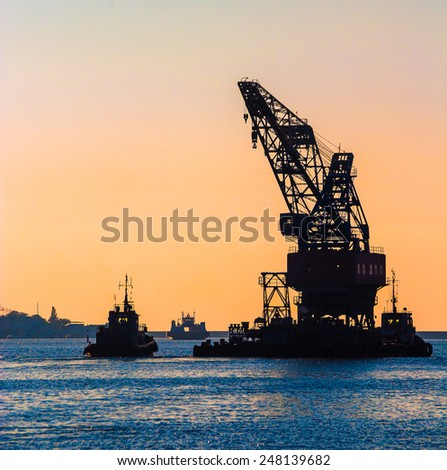 Construction works in the sea at the offshore platform. Skyline with silhouette of marine crane platform and barge. Industrial landscape - sea port at sunset. - stock photo