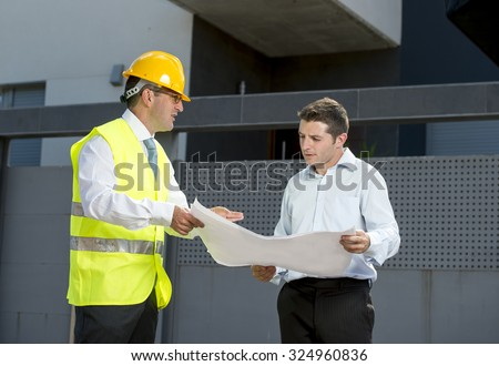 constructor manager with vest and helmet talking with customer on new house blueprint outdoors at the building door discussing final details on the construction - stock photo