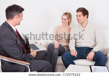 Consultant Advising Young Couple Sitting On Couch At Home - stock photo