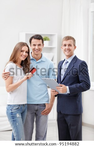 Consultant and a couple with credit card - stock photo
