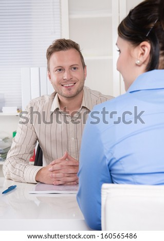 Consultant - business man sitting at desk listening to a business woman or customer - stock photo