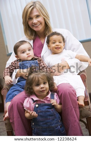 Consultant holding three IVF conceived children - stock photo