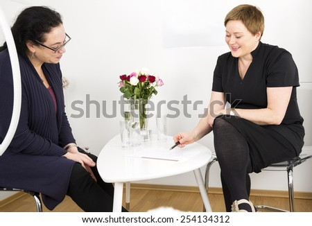 Consultation with customer at body shape clinic - stock photo