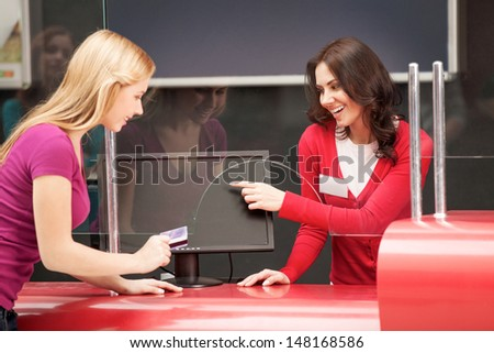 Consulting about the movies. Beautiful young women consulting cinema visitor about the movies and pointing monitor - stock photo