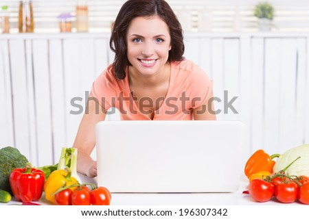Consulting online about cooking. Attractive young woman using laptop and smiling while leaning at the kitchen table with colorful vegetables laying near her  - stock photo