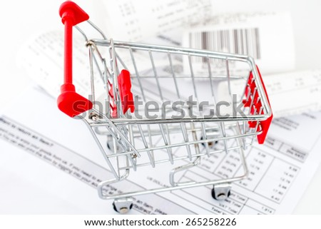 Consumerism concept. Shopping cart with receipts on white background  - stock photo