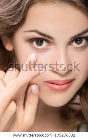 contact lens on finger of young woman looking on camera - stock photo