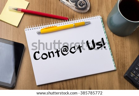 Contact us!  - Note Pad With Text On Wooden Table - with office  tools - stock photo