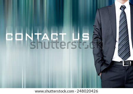 CONTACT US sign on motion blur abstract background with standing businessman - stock photo