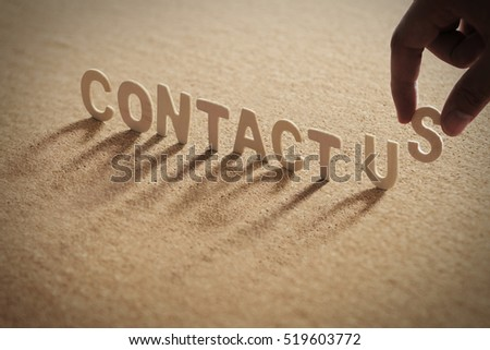 CONTACT US word of wood alphabet with shadow on cork board,compressed board