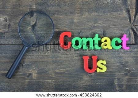 Contact us word on wooden table - stock photo