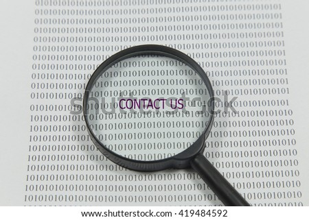 contact us word under torn black sugar paper with a magnifying glass