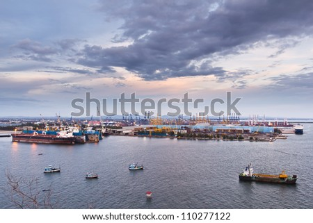 container and crane in shipyard on the sea at twilight