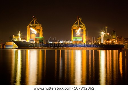Container Cargo freight Industrial ship with working crane bridge unloading and loading goods in Bangkok shipyard Terminal at night for Logistic Import Export background - stock photo