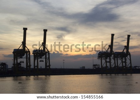 Container Cargo freight ship with working crane bridge - stock photo