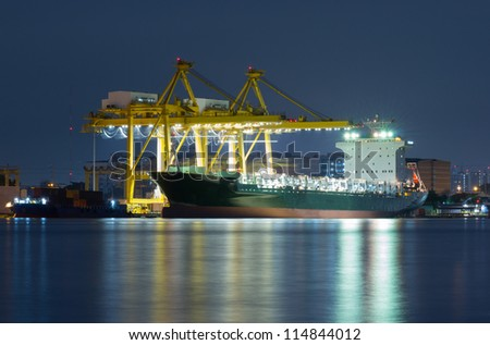 Container Cargo freight ship with working crane bridge in shipyard at dusk for Logistic Import Export background nearby river - stock photo