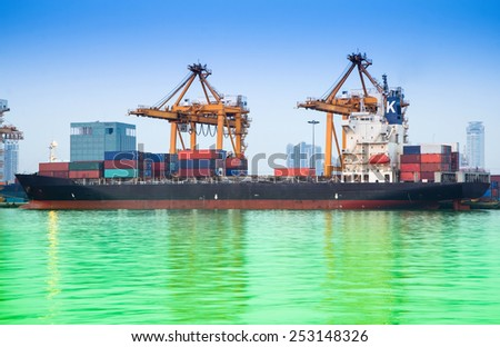 Container Cargo freight ship with working crane bridge in shipyard at evening for Logistic Import Export background - stock photo