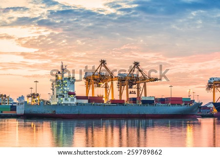 Container Cargo freight ship with working crane bridge in shipyard at Logistic Import Export Zone background with sunrise - stock photo