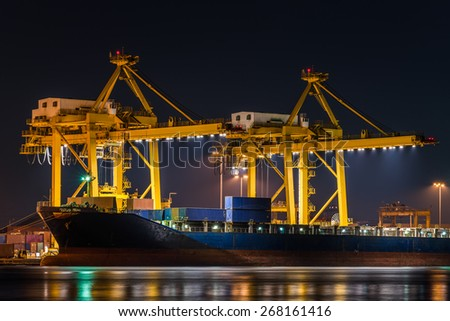 container cargo freight ship with working crane bridge in shipyard at night for logistic import export - stock photo