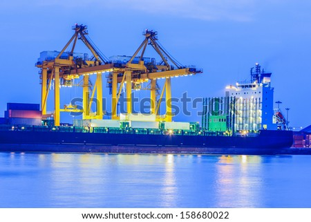 Container Cargo freight ship with working crane bridge in shipyard at twilight - stock photo