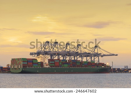 Container Cargo freight ship with working crane loading bridge in shipyard at dusk. - stock photo