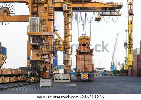 Container Cargo freight ship with working crane loading bridge in shipyard at dusk for Logistic Import Export Zone background - stock photo
