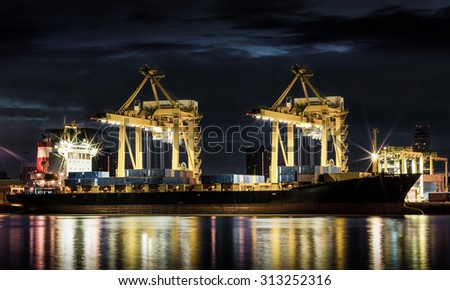 Container Cargo freight ship with working crane loading bridge in shipyard at dusk for Logistic Import Export background
