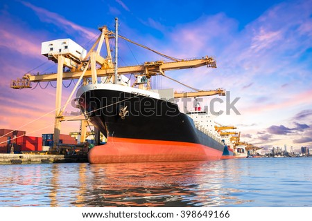 Container cargo freight ship with working crane loading bridge in shipyard at twilight for logistic Import export background - stock photo