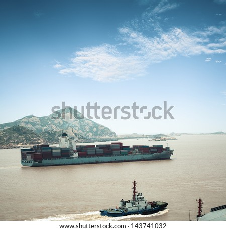 container cargo ship sailing into port - stock photo
