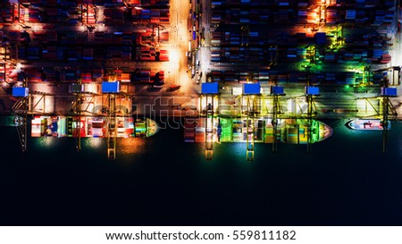 container,container ship in import export and business logistic.By crane ,Trade Port , Shipping.cargo to harbor.Aerial view.Top view.During the night
