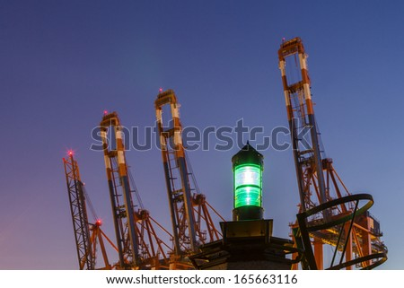 Container Cranes with Green Beacon at twilght hour - stock photo