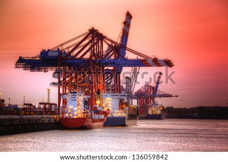 Container harbor in Hamburg, Germany. Night shoot with red sky. - stock photo