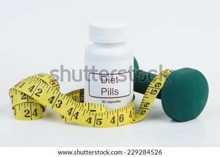 Container of diet pills with yellow tape measure and weight. - stock photo