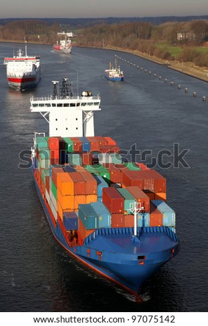 container ship and freighters on Kiel Canal, Germany - stock photo