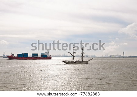 container ship and sailboat on there way to the sea - stock photo