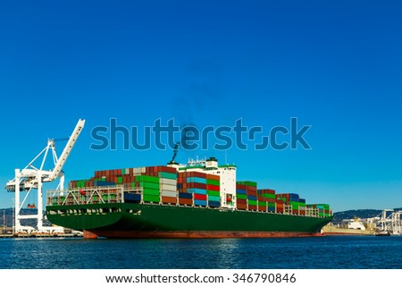 Container ship in a harbor with crane - stock photo