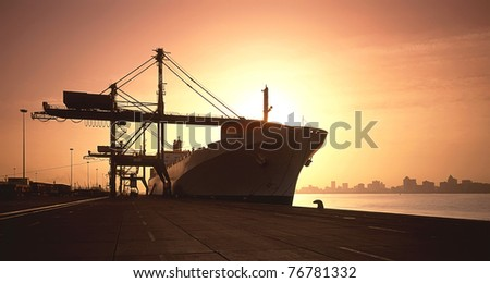 container ship offloading in harbor - stock photo