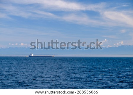 Container ship with mountains on the horizon - stock photo