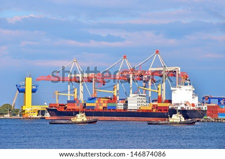 Container stack, tugboat and ship under crane bridge
