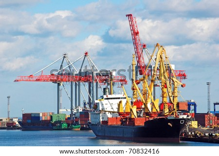 Container stacks and ship under crane bridge - stock photo