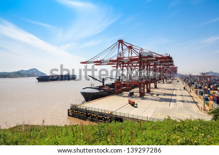 container terminal closeup and oceangoing freighter - stock photo
