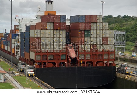 Container vessel of the panamax class squeezing through Miraflores locks of the Panama Canal - stock photo