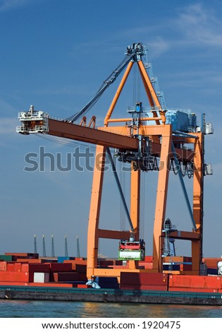 Containers being loaded into cargo vessels at Antwerp harbor (all brand names and logos have been systematically removed) - stock photo
