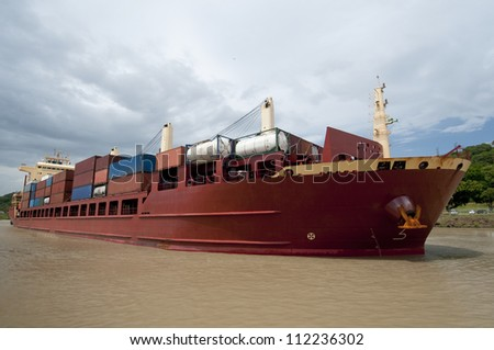Containers cargo ship navigating on waters of the Panama Canal. Panama , Central America - stock photo