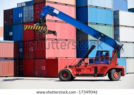 containers stacked in port with container handler / forklift on the move - stock photo