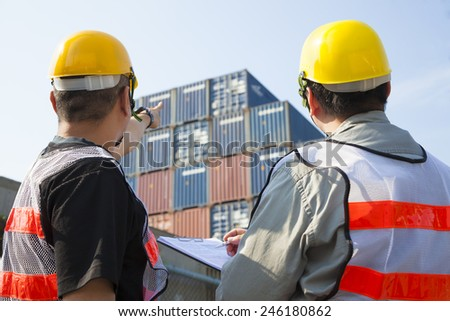 containers workers discussion and pointing for inspection