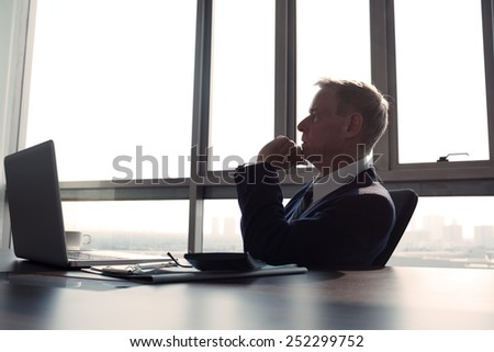 Contemplating businessman in the office, side view - stock photo
