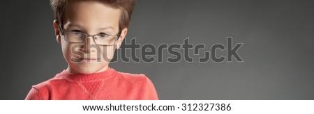 Contemplating little boy in glasses. Studio shot portrait over gray background. Fashionable little boy. - stock photo